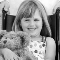 Photo d'une jeune fille handicapée assise dans un fauteuil roulant